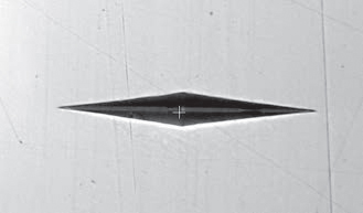 A Knoop indentation, as it appears on a smoothly polished surface, showing good tip definition.