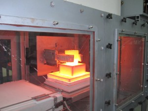 Inert atmosphere batch melt furnace featuring robotic operation and featuring molydisilicide heating elements