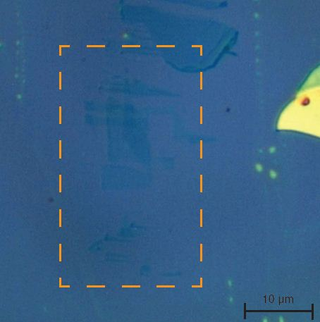 An optical microscope image of a silicon wafer coated with discrete graphene flakes. The only clearly visible features are the lighter areas to the right of the image. These contain multiple-layer graphene, which is of little interest to researchers. It is unclear from this image if graphene is located in the highlighted rectangular area.