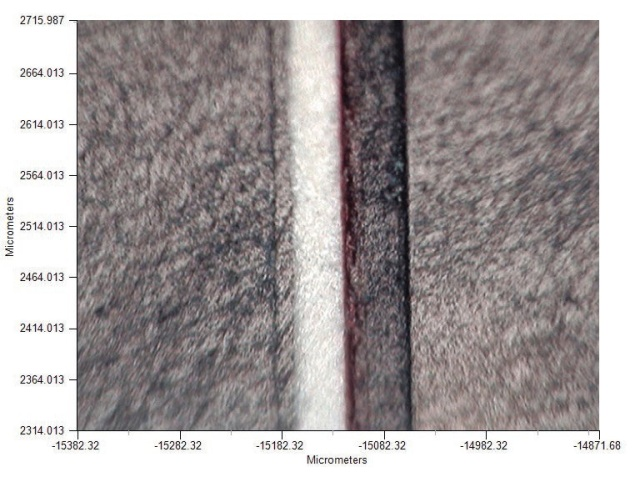 Visible image of a cross section of a paint chip embedded in resin for ATR measurements.
