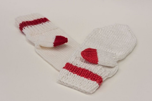A prototype mitten made from the yarn on the right, next to one made from merino wool.