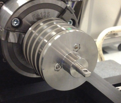 Metal corrosion coupons mounted on a cylindrical jig on the NPFLEX rotational stage chuck.
