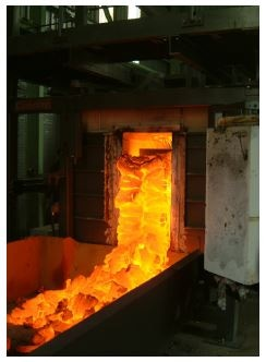 Moving wall coke oven discharging.