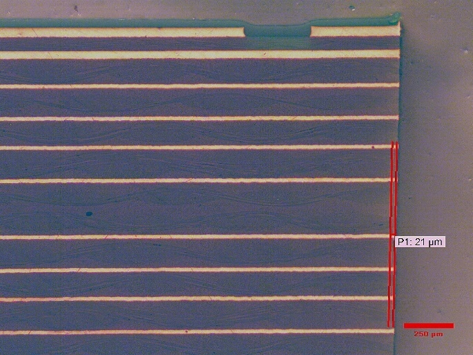 Damage from IsoMet High Speed Pro sectioning with IsoMet 15HC blade. * Note copper and board layers are parallel with little damage to the glass bundles. Damage extending ~20 microns (0.02 mm) from the edge of the cut.