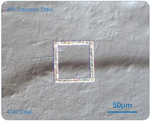 An optical micrograph of a cross-section of a 410 stainless steel/4140 steel laser beam welded interface. Nanoindentation was carried out within the focused ion beam (FIB) ablated square. Note: The nanoindentation grid is not visible.