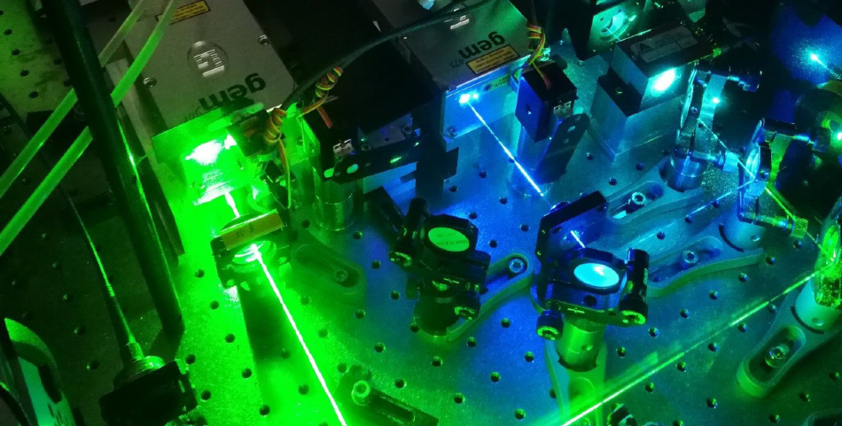 Photograph of the laser compartment of a widefield microscope for SMLM with the beam paths of the gem 473 (blue) and gem 561 (lime).