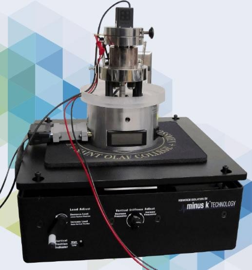 The nanoindenter-quartz microbalance mounted on a negative-stiffness vibration isolator