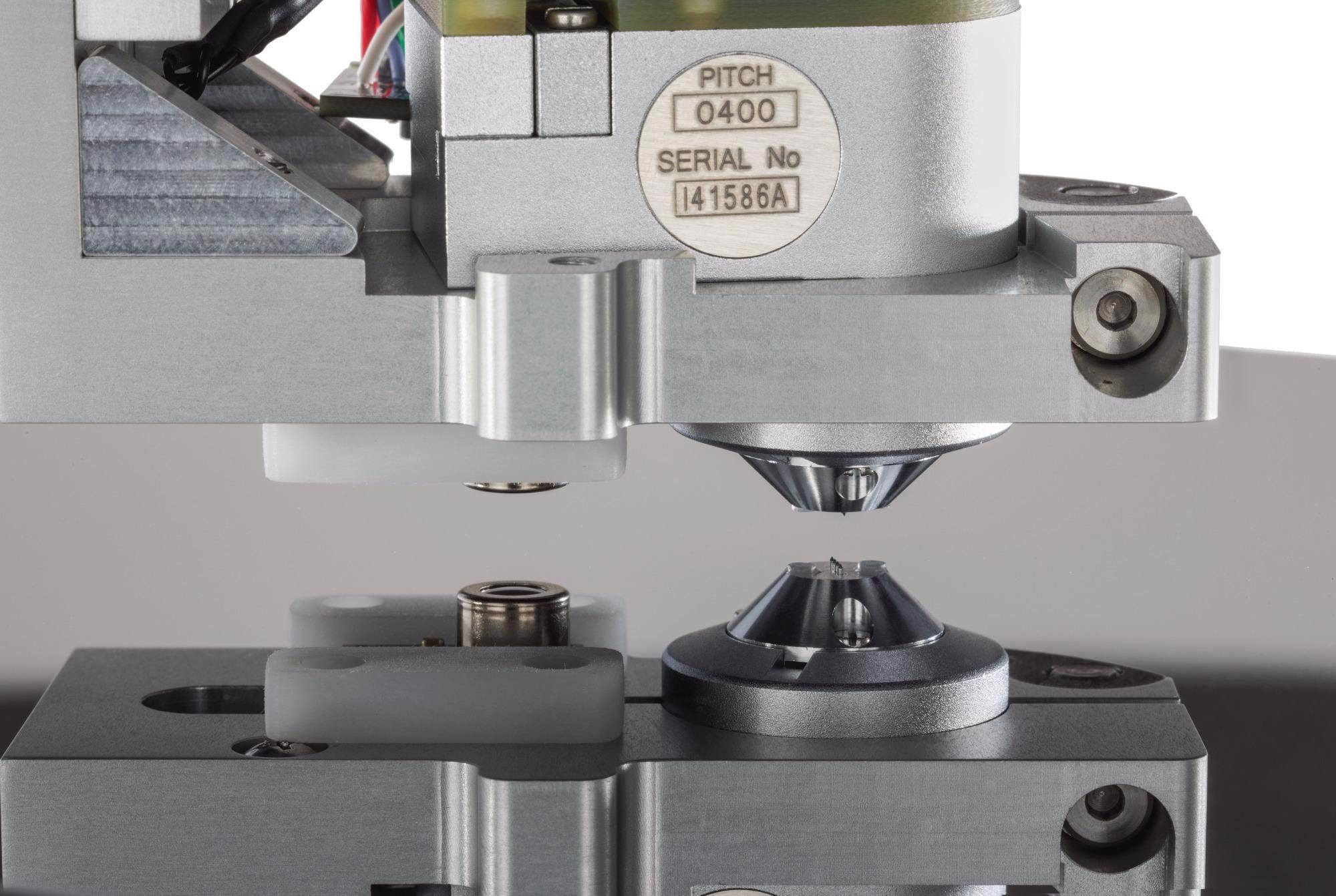 The R50 four-point probe approaches the surface of a conductive layer.